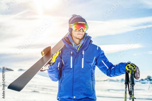 Skier ready holding skiing equipment with sun back light on ski slope