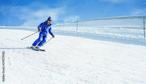 Young athlete skiing in alps mountains on weekend day - Skier riding down in winter snow resort for holidays time - Sport competition, travel, training and vacation concept - Focus on his head