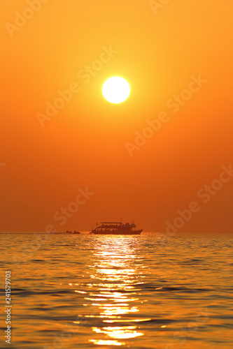 Sunset seascape with boat and jet skis in Thailand