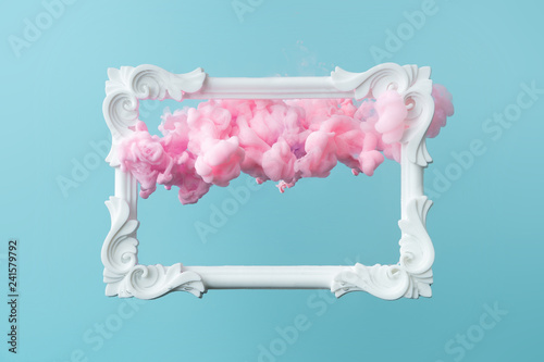 Foto White vintage frame on pastel blue background with abstract pink cloud shapes