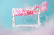 Leinwanddruck Bild - White vintage frame on pastel blue background with abstract pink cloud shapes. Minimal border composition.