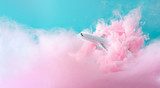 Passenger jet airplane flying through pastel pink clouds. Minimal transportation, travel or vacation concept. - 241580163