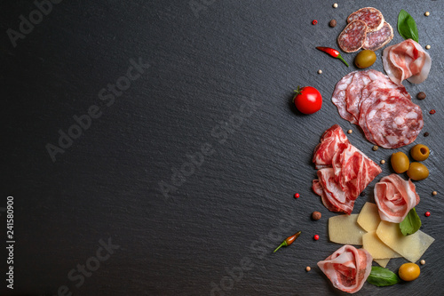 flat lay of antipasti with salami, cheeses, prosciutto, ham, olives, greens, tomato on black slate background, copy space