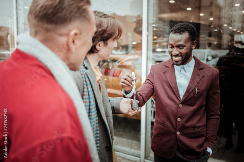 Valokuva  Dark-haired young man taking car keys form smiling sales consultant