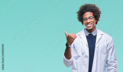Afro american doctor scientist man over isolated background smiling with happy face looking and pointing to the side with thumb up Fototapet