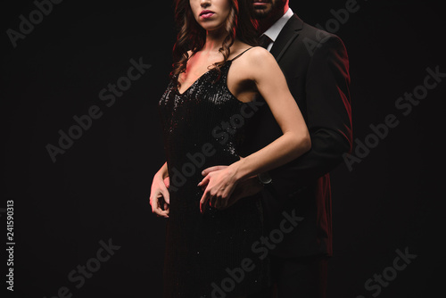 cropped view of sexy couple posing in black dress and tuxedo isolated on black