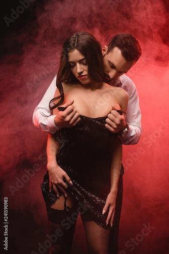 Fototapeta handsome passionate boyfriend undressing attractive girl in red smoky room obraz