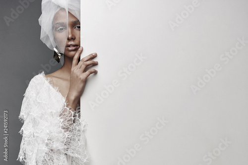 Fotografija  Studio portrait of woman with white make up, in white lace dress, white veil head tie and big earring