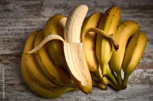 Fotografía  bunch of tasty ripe yellow bananas on a light wooden board