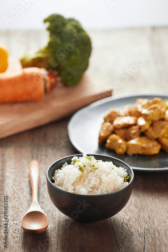 Photo  White rice with curry and chicken in black plate on wooden table