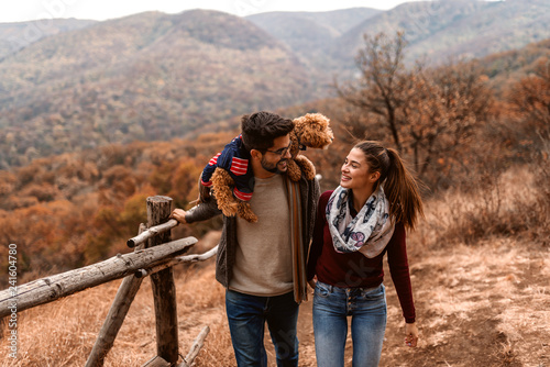 Couple taking a walk in nature. On man's shoulders poodle. In background mountains and forest. Autumn time.