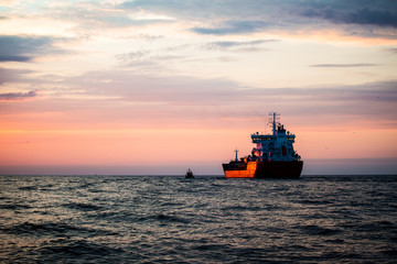 Colorful sunset over the Baltic sea and cargo ship on a background, Latvia