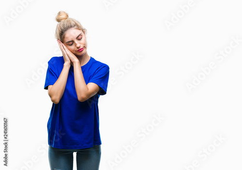Fototapeta  Young beautiful blonde and blue eyes woman wearing blue t-shirt over isolated background sleeping tired dreaming and posing with hands together while smiling with closed eyes
