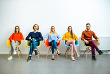 Portrait Of A Young People Dressed Casually Sitting In A Row On The Colorful Chairs On The White Wall Background