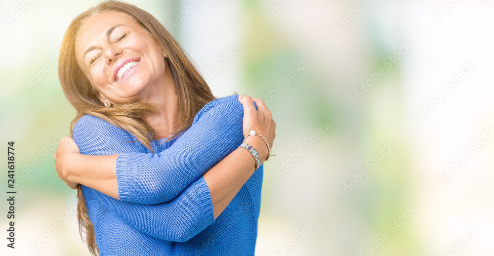 Fototapeta Middle age beautiful woman wearing winter sweater over isolated background Hugging oneself happy and positive, smiling confident. Self love and self care