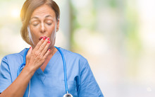 Middle Age Senior Nurse Doctor Woman Over Isolated Background Bored Yawning Tired Covering Mouth With Hand. Restless And Sleepiness.