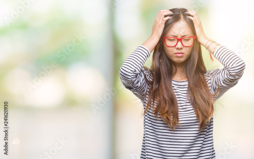 c4ba1ad8568 Young asian woman wearing glasses over isolated background suffering from  headache desperate and stressed because pain and migraine. Hands on head.