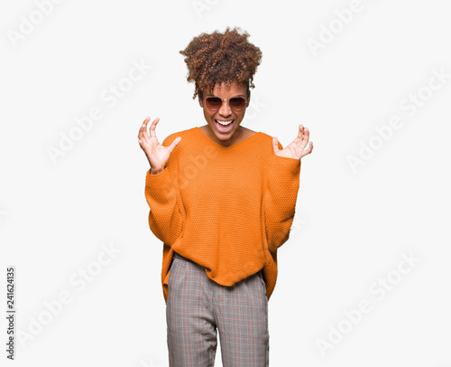 Autocollant pour porte Doux monstres Beautiful young african american woman wearing sunglasses over isolated background crazy and mad shouting and yelling with aggressive expression and arms raised. Frustration concept.