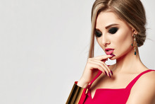 Young Sensual Beautiful Woman Posing In Fashion Red Dress And Big Gold Bracelet Looking Down