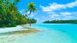 AERIAL: Young female tourist in bikini walking along the white sand shoreline.