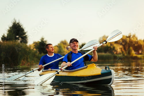 Young men rowing kayak on river at sunset. Couple of friends having fun canoeing in summer