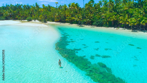 Foto auf AluDibond Turkis DRONE: Tourist girl in bikini walks into the shallow turquoise ocean water.