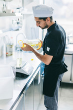 Chef Measuring Cooking Oil On Weight Scale In Commercial Kitchen At Pizzeria