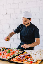 Chef Pouring Cooking Oil On Pizza Against Wall In Commercial Kitchen At Pizzeria