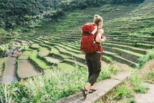 Full Length Of Female Hiker With Backpack Walking On Terrace Field In Village