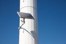 Low Angle View Of Solar Panel On Windmill Against Clear Blue Sky