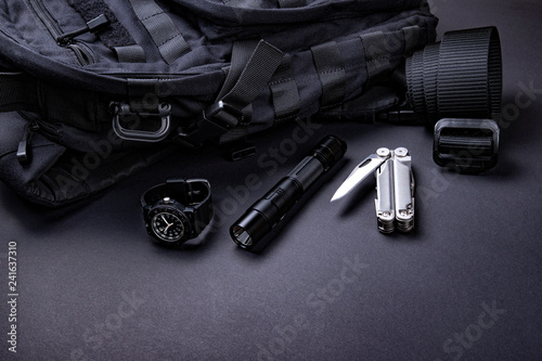Fotomural Everyday carry (EDC) items for men in black color - backpack, tactical belt, flashlight,  watch and silver multi tool
