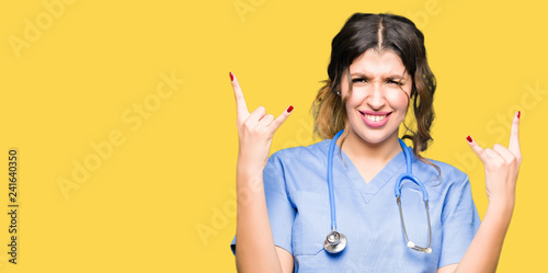 Valokuva  Young adult doctor woman wearing medical uniform shouting with crazy expression doing rock symbol with hands up