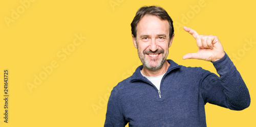 Valokuva  Middle age handsome man wearing a sweater smiling and confident gesturing with hand doing size sign with fingers while looking and the camera