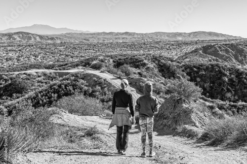 Fotografia, Obraz  Mother and daughter stand above a city in mountains