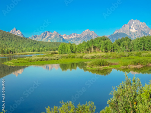 Poster Bergen Grand Teton National Park, Wyoming, United States. Scenic landscape of Teton Range of the Rocky Mountains reflecting in the calm waters of Jackson Lake. North America in summer blue sky, copy space.