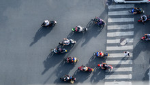 Top Aerial View Of Blur Bikers Ride The Motorcycles To Pass Pedestrian Crosswalk On Road With The Traffic Pattern Signage On The Street