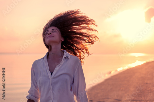 Fotografía Beautiful young woman girl with flying curly hair on the background of a tropica