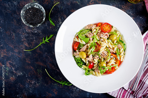 Pasta salad with tuna, tomatoes, olives, cucumber, sweet pepper and arugula on rustic background . Top view