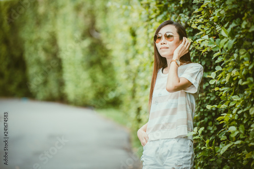 Valokuva  asian thin hipster girl wearing sunglasses in the green park relax holiday vinta