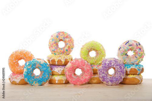 Many colorful frosted cake donuts with candy sprinkles stacked and up on side laying on wood table isolated on white background. Fun festive party food.