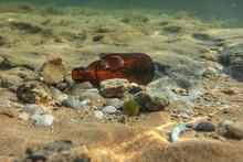Underwater Photo, Discarded Small Beer Bottle On Sea Floor. Ocean Littering Concept.