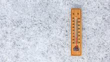 Wooden Thermometer Showing Low Temperature Laying On Flat Ice Ground Made Of Crystals. Winter Weather Concept.