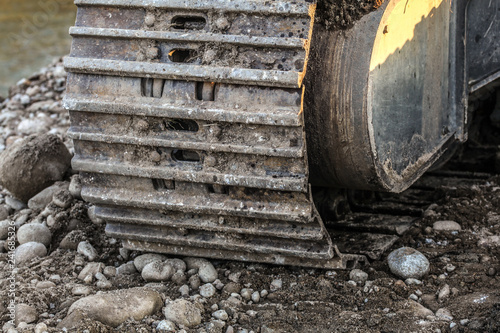Fotografie, Obraz  Detail of metal digger track on stones and sand ground