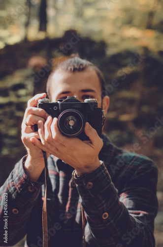 Fototapeta Nature Photography Concepts Professional photographer: stylish bearded man, dressed in a shirt and with a hairdo Top Knot with retro photo camera in hands takes pictures in the woods obraz na płótnie