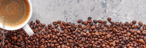 Coffee cup with roasted beans on stone background. Panoramic top view with copy space for your text.