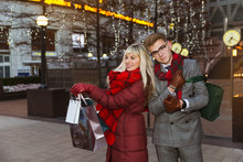 The Joyful Young Couple Standing In The Street With Shopping Bags After Good Shopping