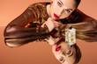 beautiful woman with glamorous makeup, perfume bottle and mirror reflection posing isolated on orange