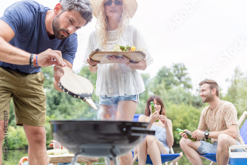 Man using bellows for preparing food in barbecue grill with friends on pier Canvas Print