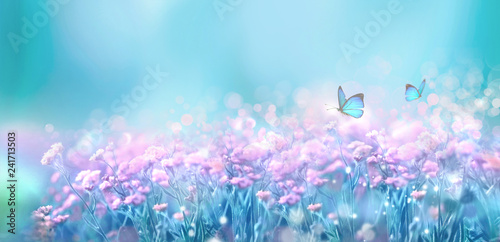 Fotobehang Lente Floral spring natural landscape with wild pink lilac flowers on meadow and fluttering butterflies on blue sky background. Dreamy gentle air artistic image. Soft focus, author processing.