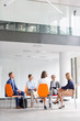 Colleagues planning strategy while sitting on chairs during meeting